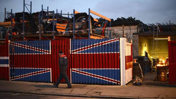 A man walks past a car scrap yard in east London Jan. 25, 2013. Britain's economy shrank more than expected at the end of 2012 as a North Sea oil production slump, lower factory output and a hangover from London's Olympics took effect. (PAUL HACKETT/Reuters)