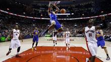 Golden State Warriors Harrison Barnes (C) goes up for a slam dunk past Toronto Raptors Terrence Ross (R) during the second half of their NBA game in Toronto January 28, 2013. (MARK BLINCH/REUTERS)