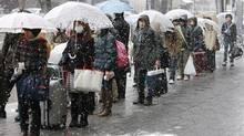 People stand in driving snow as they queue for a bus to leave town in Sendai, Japan, Thursday, March 17, 2011. (Mark Baker/Mark Baker/The Associated Press)
