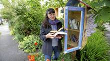 Angela Evans of Victoria checks out some books in the book-exchange box she made outside her home on Saturday. She and her neighbours on Clare Street have been trying to renew their sense of community by using the box to share reading material. (Deddeda Stemler for The Globe and Mail)