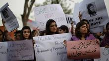 "Pakistani women, hold banners during a protest condemning the attack on schoolgirl Malala Yousufzai, in Islamabad, Pakistan, Wednesday, Oct. 10, 2012. Pakistani doctors successfully removed a bullet Wednesday from the neck of a 14-year-old girl who was shot by the Taliban for speaking out in support of education for women, a government minister said. Banner bottom right reads, "" The Taliban is afraid of an unarmed girl."" (Muhammed Muheisen/AP)"