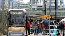 Passengers board a streetcar near the Olympic Village Canada Line Station in Vancouver. Two streetcars, on loan from the Brussels Transport Co., will provide free rides from the Olympic Village Canada Line Station to Granville Island. (DARRYL DYCK)