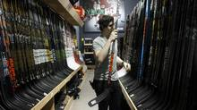 An employee sorts Bauer hockey sticks displayed for sale at an equipment store in Mississauga on Oct. 31, 2016. Performance Sports Group Ltd., the owner of the Bauer and Easton brands, filed for bankruptcy protection as part of a deal to sell the hockey- and baseball-equipment business for at least $575 million. (Cole Burston/Bloomberg)