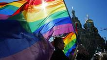 Gay rights activists carry rainbow flags as they march during a May Day rally in St. Petersburg on May 1, 2013. (DMITRY LOVETSKY/ASSOCIATED PRESS)
