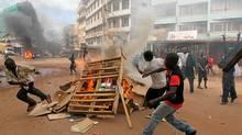 Rioters fuel a burning barricade during riots in Kampala on April 29, 2011, a day after Uganda's opposition leader Kizze Besigye was arrested (MARC HOFER/MARC HOFER/AFP/Getty Images)
