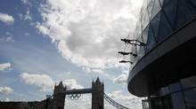 Members of the Streb extreme dance group abseil down the face of City Hall, with Tower Bridge and the Olympic rings behind them in central London, July 15, 2012. (Reuters)