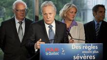 Quebec Liberal Party Leader Jean Charest, flanked by candidates, responds to reporters questions at a news conference during a campaign stop in Quebec City. (JACQUES BOISSINOT/THE CANADIAN PRESS)