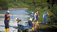 Workers clean oil from the banks of the Kalamazoo River in Marshall, Mich., in July after an Enbridge pipeline ruptured. (Kevin Van Paassen/Kevin Van Paassen/The Globe and)