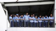 Workers on strike stand on a balcony inside the Omron Automotive Electronics Co. Ltd. plant in Guangzhou July 21, 2010. (STRINGER BEIJING/REUTERS)