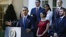 U.S. President Barack Obama stands with Affordable Care act registrants and beneficiaries as he speaks about health care from the Rose Garden of the White House. (JASON REED/REUTERS)