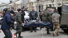 Forensic experts carry the body of Denis Voronenkov, after he was shot dead in Kiev, Ukraine, Thursday, March 23, 2017. (AP/Sergei Chuzavkov)