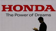 A man is silhouetted against a logo of Honda Motor at the company showroom in Tokyo January 31, 2012. (Toru Hanai/Toru Hanai/REUTERS)