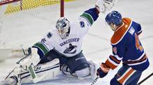 Vancouver Canucks' Jacob Markstrom makes the save on Edmonton Oilers' Taylor Hall during second period NHL hockey action in Edmonton on April 12 (JASON FRANSON/THE CANADIAN PRESS)