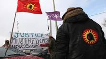 Native protesters rise a banner during a blockade at the VIA train tracks at Wyman's Road near Shannonville, Ont., on March 19, 2014. The protesters want justice for murdered and missing indigenous women. (LARS HAGBERG/THE CANADIAN PRESS)