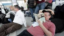 Philadelphia-bound traveller Kevin Wall, right, reads a book as thousands of passengers wait in line to board U.S. bound flights at Toronto's Pearson International airport on Dec. 27, 2009. (J.P. MOCZULSKI/J.P. MOCZULSKI/THE GLOBE AND MAI)