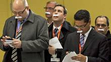 Reporters on NDP Leader Jack Layton's campaign tour sport paper moustaches as an April Fool's joke in Sudbury on April 1, 2011. (Andrew Vaughan/THE CANADIAN PRESS)
