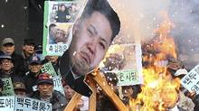 A portrait of North Korean leader Kim Jong Un is burned by protesters during an anti-North Korea rally marking the second anniversary of former North Korean leader Kim Jong Il's death in Seoul on Dec. 17, 2013. (Ahn Young-joon/AP)