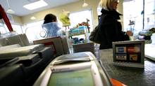 A sign showing Visa, Mastercard, Amex and Interac on the counter at Baby on The Hip, on Queen Street East in Toronto. (Deborah Baic/Deborah Baic/THE GLOBE AND MAIL)