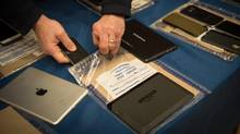 Encrypted smartphones held as evidence by the New York City Police Department are displayed at a news conference in New York, Feb. 18, 2016. Apple in the past has frequently helped the Justice Department unlock iPhones, but last fall, in connection with a routine drug case, it refused, foreshadowing a showdown with the Obama administration over the locked iPhone belonging to one of the San Bernardino shooting rampage suspects. (BRYAN R. SMITH/NYT)