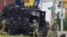Emergency response officers enter a residence in Moncton, N.B., Thursday, clockwise from top, searching for a suspect who killed three Royal Canadian Mounted Police officers in a shooting the day before. (Andrew Vaughan/The Associated Press)