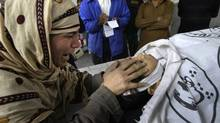 Rukhsana Bibi grieves as she touches the body of her daughter, polio worker Madiha Bibi, killed by unknown gunmen, at a morgue of local hospital in Karachi, Pakistan, Dec. 18, 2012. (Fareed Khan/AP)