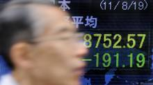 A man walks past an electric quotation board flashing the Nikkei key index of the Tokyo Stock Exchange in front of a securities company in Tokyo on Aug. 19, 2011. (Toru Yamanaka/AFP/Getty Images/Toru Yamanaka/AFP/Getty Images)