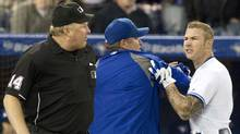 Toronto Blue Jays Manager John Farrell restrains Brett Lawrie (right) as he confronts Home Plate Umpire Bill Miller (left) ) as the third baseman contests a strike out call during the ninth inning of MLB baseball action against Tampa Bay Rays in Toronto on Tuesday May 15 , 2012. (Chris Young/THE CANADIAN PRESS/Chris Young/THE CANADIAN PRESS)