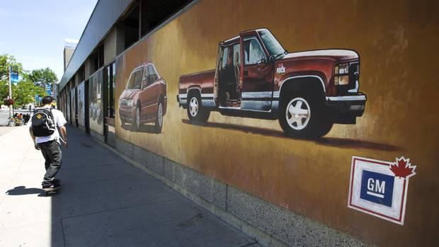 Pedestrians in downtown Oshawa, Ont. pass by murals painted on the walls of the bus station on July 20, 2013.