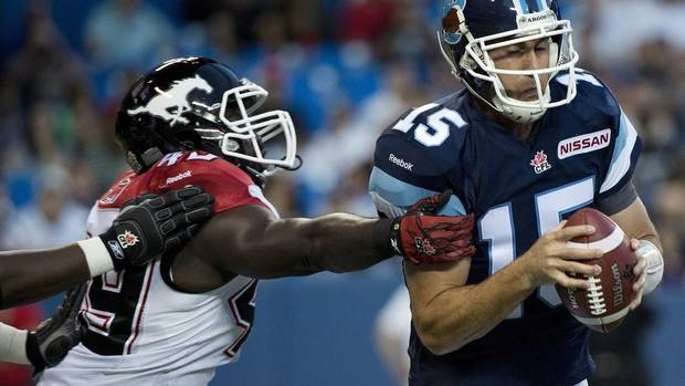 Toronto Argonauts quarterback Ricky Ray, right, avoids a tackle by Calgary Stampeders defensive linemen Cordarro Law, left, during first half CFL football action in Toronto, on Friday, August 23, 2013. Ray left the game. (NATHAN DENETTE/THE CANADIAN PRESS)