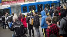 People line up in Vancouver to board a 99 B-Line TransLink bus on West Broadway on Wednesday. (DARRYL DYCK/THE GLOBE AND MAIL)