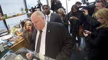 Reporters surround mayor Rob Ford and councillor Frances Nunziata, left, in a coffee shop adjacent to the Toronto Community Housing Corporation (TCHC) headquarters where the corporation's board held a special meeting in Toronto on Friday, April 25, 2014. The TCHC board announced the firing of its CEO Gene Jones. (Darren Calabrese)