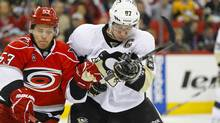 Sidney Crosby and Carolina Hurricanes centre Jeff Skinner battle for puck in Raleigh, N.C. on Dec. 3, 2011. (James Guillory/US PRESSWIRE/James Guillory/US PRESSWIRE)