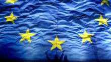 Cheering Romanians cast shadows on a giant European Union flag on Jan. 1, 2007. (VADIM GHIRDA/Vadim Ghirda/AP)