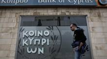 A man walks past a branch of Bank of Cyprus in Nicosia March 31, 2013. (YORGOS KARAHALIS/REUTERS)