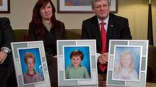 Darcie Clark's cousin Stacy Galt sits with Prime Minister Stephen Harper before he announced the government is providing courts with new powers to lock up people found not criminally responsible for their crimes due to mental problems in Burnaby on Feb. 8, 2013. Darcie Clark's children Max, Cordon and Kaitlynne were killed by her ex-husband Allan Schoenborn in 2008. (DARRYL DYCK/THE CANADIAN PRESS)
