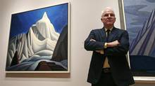 """Actor and comedian Steve Martin, who is guest curator of an exhibition at the Museum of Fine Arts devoted to Canadian modernist Lawren Harris, stands next to Harris's """"Mountain Forms"""" painting, left, during a gallery preview at the museum in Boston, Friday, March 11, 2016. (Charles Krupa/The Associated Press)"""