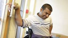 Harmandeep Saini, 25, works on opening and going through doors with his Physio/Occupational Therapy Assistant Heather Densmore. (Peter Power/The Globe and Mail/Peter Power/The Globe and Mail)