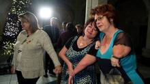 Myriam Bouffard of Quebec City, right, embraces Aline Vachon after MPs voted unanimously to support thalidomide survivors. (Dave Chan for The Globe and Mail)
