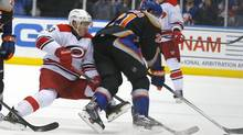 Carolina Hurricanes left wing Jeff Skinner (53) checks New York Islanders right wing Kyle Okposo (21) in the third period of an NHL hockey game in Uniondale, N.Y., Saturday Jan. 4, 2014. (Paul Bereswill/AP)