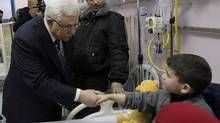 Palestinian President Mahmoud Abbas visits a Palestinian boy, one of dozens of schoolchildren injured in a school bus accident, at a hospital in the West Bank city of Ramallah, Feb. 16, 2012. (Nasser Shiyoukhi/AP/Nasser Shiyoukhi/AP)