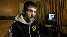 Tamas Miko, sits in his small motel room somewhere in Ontario, hiding from the associates of the human trafficking ring in Hamilton, that he fell victim to upon his arrival in Canada. (Glenn Lowson/The Globe and Mail)