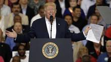 President Donald Trump gestures as he holds up a piece of paper on the presidential powers on immigration during a campaign rally on Feb. 18, 2017, at Orlando-Melbourne International Airport, in Melbourne, Fla. (Chris O'Meara/AP)