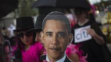 """Members of CodePink, an anti-war group mainly composed of women, wave images of U.S. President Barack Obama (C) and Republican presidential candidate Mitt Romney (L) as they protest against """"Money and politics,"""" near the venue for the upcoming Democratic National Convention in Charlotte, North Carolina on Sept. 2. (ADREES LATIF/REUTERS)"""