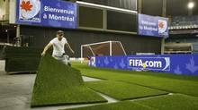 A worker puts down turf at Olympic Stadium in Montreal in preparation for the FIFA U-20 World Cup soccer tournament, June 28, 2007. (Shaun Best/Reuters)