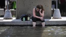 The waters of the reflecting pool at Nathan Phillip Square offers a cooling break for this woman as she soaks her feet in the water during a lunch break on June 20 2012. (Fred Lum/Fred Lum/The Globe and Mail)