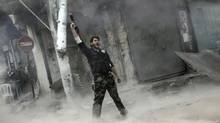 A rebel fighter gestures for victory after firing a shoulder-fired missile toward a building where Syrian troops loyal to President Bashar Assad were hiding as they attempted to gain terrain against the rebels during heavy clashes in the Jedida district of Aleppo, Syria, Nov. 4, 2012. (Narciso Contreras/AP)