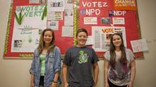 Chaya Rasmidatta (left) stands in front of her Green Party poster that she made along with Ben Horodyski and Abbey O'brien in front of their NDP poster in Kerrisdale Elementary School in Vancouver, Wednesday May 8, 2013. (Eric Dreger/THE CANADIAN PRESS)
