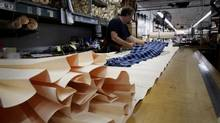 An employee rolls up fabric for a pleat mold that will be steam baked to hold the form at the Dennis Uniform Manufacturing Co. facility in Portland, Oregon, U.S., on Monday, Aug. 25, 2014. (Meg Roussos/Bloomberg)