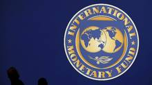Visitors are silhouetted against the logo of the International Monetary Fund at the main venue for the IMF and World Bank annual meeting in Tokyo, October 10, 2012. (Kim Kyung Hoon/REUTERS)