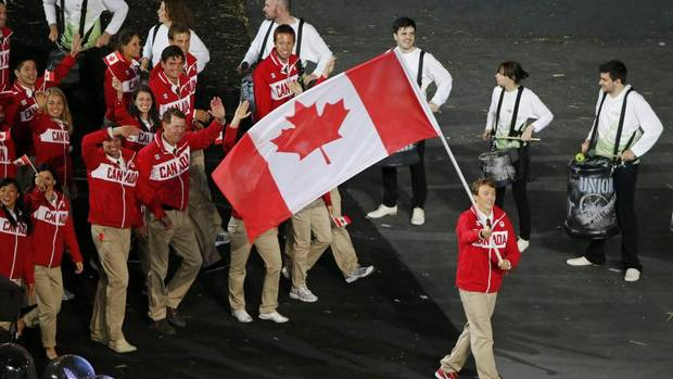 Canada's flag bearer Simon Whitfield holds the national flag as he leads the contingent in the athletes parade during the opening ceremony of the London 2012 Olympic Games at the Olympic Stadium on July 27. Mr. Whitfield is among members of Canada's Olympic triathlon team to use Stouffville, Ont.-based Saringer Life Science Technologies' Venowave medical device. (DAVID GRAY/REUTERS)